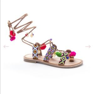 Lace up sandals with pom poms and coin details
